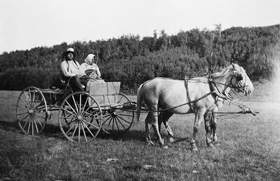 Homme et femme Niitsítapi se déplacant en chariot tiré par deux chevaux.