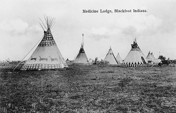 Photographie d'un campement Niitsítapi composé de plusieurs tipis.