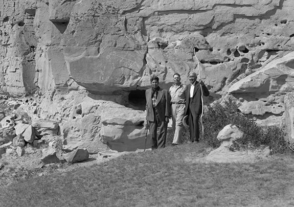 The image shows two members of the Niitsítapi (Blackfoot) Nation and a third unidentified individual posing in front of a few rock carvings at Áísínai'pi