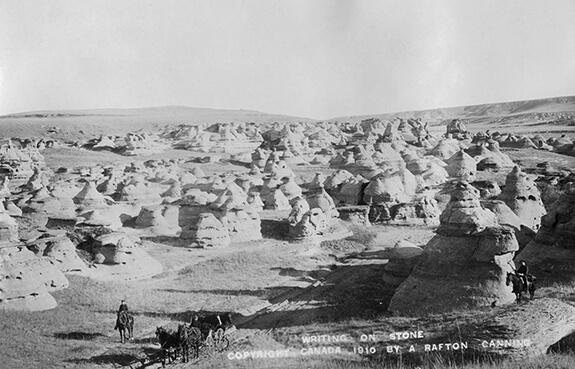 Photographie du paysage à Áísínai'pi avec des cavaliers et un chariot.