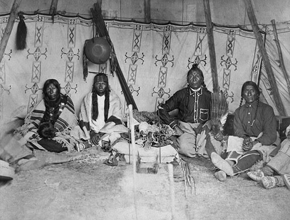 Photographie d'un groupe d'hommes assis dans un tipi.