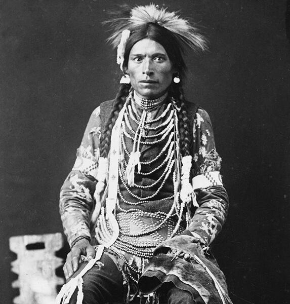 Portrait d'un jeune homme Niitsítapi assis sur une chaise portant une coiffe sur la tête et plusieurs parures au cou et sur les bras.