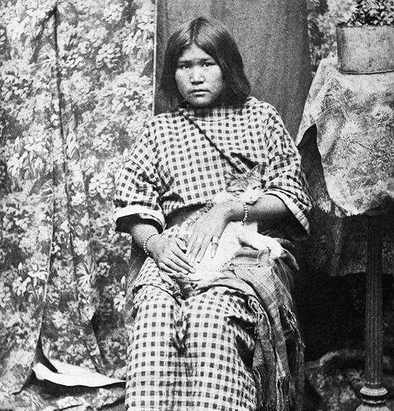 Photographie d'une jeune femme Niitsítapi assise sur une chaise et tenant un chat entre ses bras.