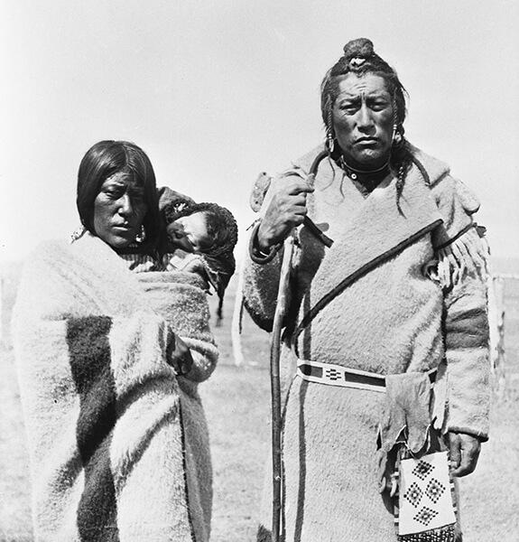 Portrait de Bull Bear et son épouse vêtus de vêtements fabriqués à partir de couvertures de la Compagnie de la Baie-d'Hudson. L'épouse porte un bébé endormi sur son dos.