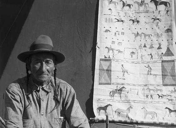 Joe Calf Child, Niitsítapi posant à côté d'une œuvre sur toile composée de différentes scènes thématiques dont la plupart représentent des chevaux.