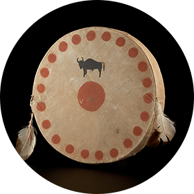 Image of a round drum with a black buffalo illustration and a red circle in the centre. The edge of the drum is decorated with several red circles. Two feathers are fastened to the drum.