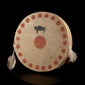 Image d'un tambour circulaire avec une illustration d'un bison noir et un cercle rouge au centre dont la circonférence est décorée avec plusieurs cercles rouges et deux plumes attachées au tambour.