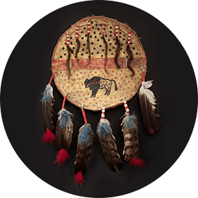 Picture of a hide shield featuring various motifs, including a buffalo. Several feathers and hair strands are fastened to the object.