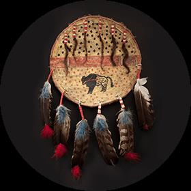 Photographie d'un bouclier de peau sur lequel apparaissent différents motifs, dont celui d'un bison. Plusieurs plumes et mèches de cheveux sont attachées à l'objet.
