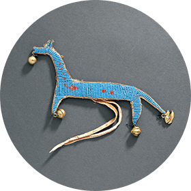 Image of a horse-shaped amulet, embroidered with blue and red glass beads and decorated with copper jingles