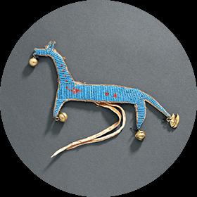 Image d'une amulette en forme de cheval, brodée de perles de verre bleues et rouges et décorée avec des clochettes de cuivre.