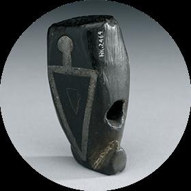 Image d'un fourneau de pipe en pierre incrusté avec une figure humaine au corps triangulaire.