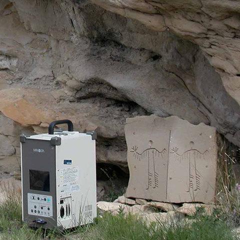 Photographie d'un homme scannant au laser deux panneaux de grès gravés avec des figures humaines identiques.