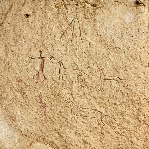 Photographie de pétroglyphes de trois chevaux, d'une figure humaine et d'un tipi.