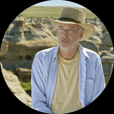 Photographie de Jack Brink avec, en arrière-plan, une partie des falaises de grès
