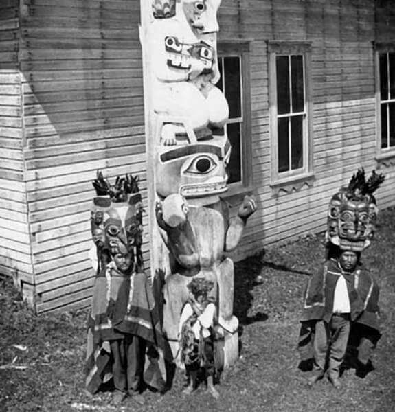 Historical picture showing a totem and a few individuals wearing ceremonial headdresses and garments