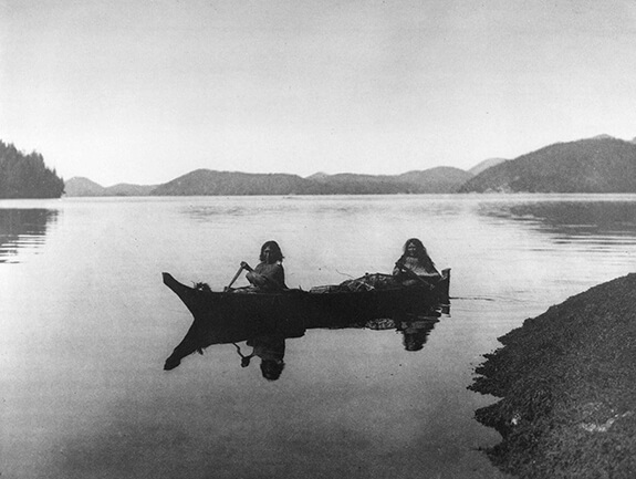 Old picture of two women in their traditional watercraft