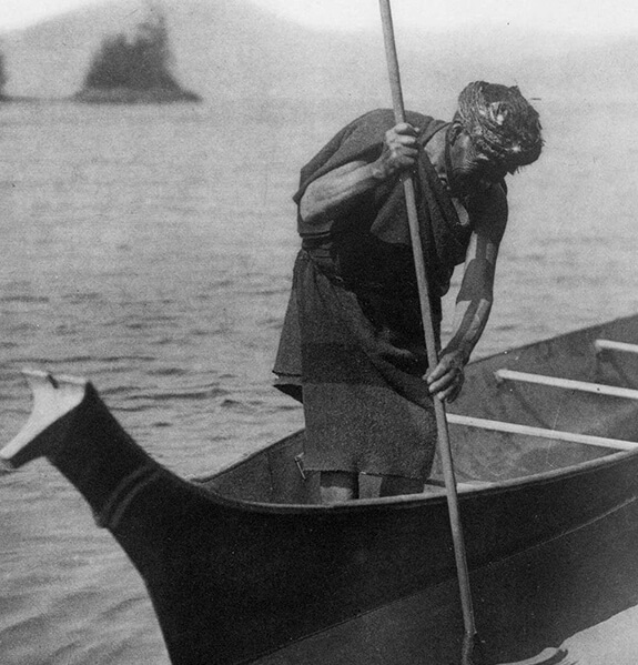 Old picture of a man standing up in his watercraft. He is using a harpoon to catch fish.