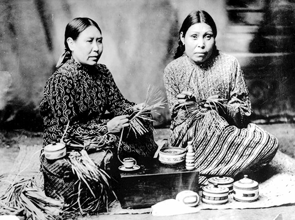 Old picture of two women from Nootka Sound weaving baskets