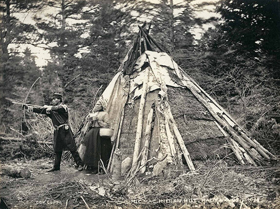 Picture of Mi'kmaq man and woman posing in front of their bark-covered wigwam