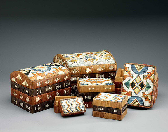 Picture of a set of six Mi'kmaq birchbark boxes adorned with porcupine quill patterns