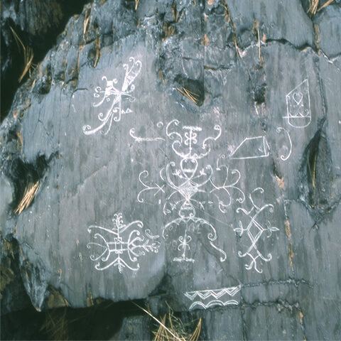 Picture of curvilinear carvings that appear to illustrate a traditional summer gathering known by the Mi'kmaq as Mawomi