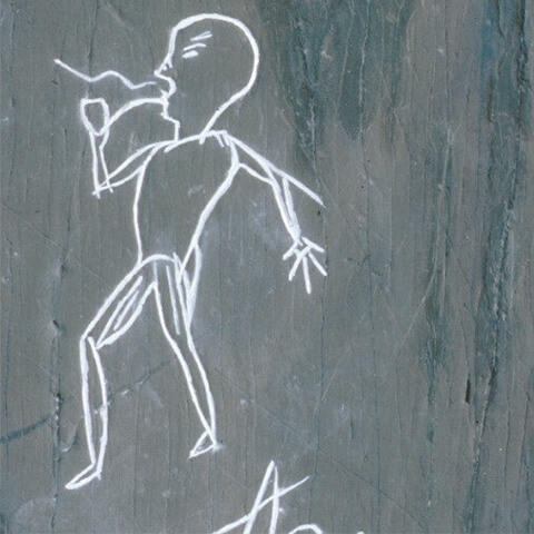 Picture of a petroglyph featuring a figure smoking a clay pipe. The year 1877 and the first name Jim were also carved in the stone.
