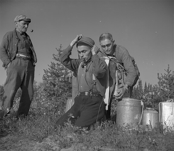 Picture of Pessamit Innu Raphael Bacon, Ignace Picard and his son Pierre. The three men are helping each other to carry loads with straps.