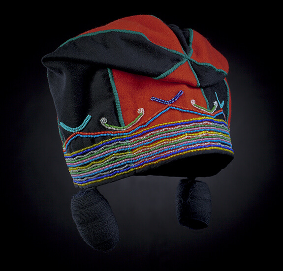 Picture of an Innu woman's cap. Made with several black and red woolen pieces, the cap features rows of glass beadwork in different colours: yellow, red, blue, pink, green, and pale blue at the bottom. Two black balls of wool are hanging on each side.