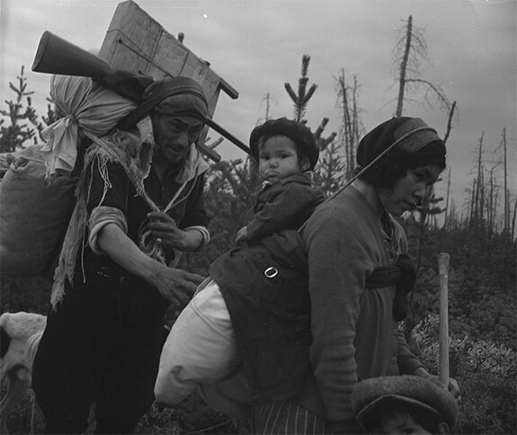 Picture of Sylvestre Kapu with his daughter and wife Hélène carrying several loads on their way to the Pessamit Innu's hunting grounds