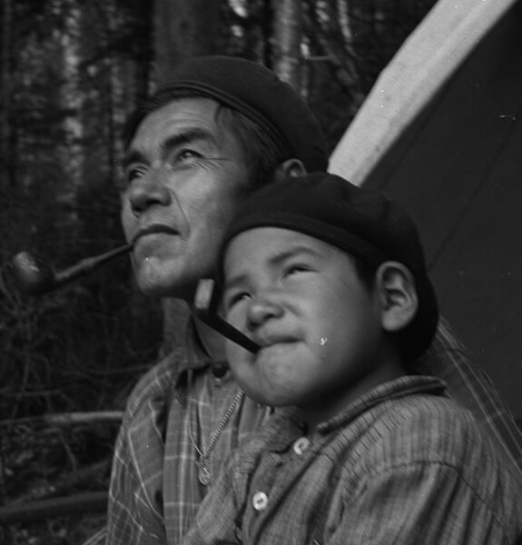 Pessamit Innu Joseph Benoît and his five-year-old son, both with a pipe in their mouths, posing for photographer Paul Provencher