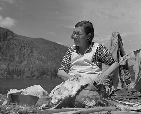 Photographie de M<sup>me</sup> Charles Fontaine plumant son huard, sur le bord d'un lac