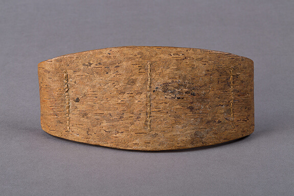 Picture of a frontal pad made with three layers of thick birch bark. The straps used by the Innu to carry their loads on their backs rested on such pads.