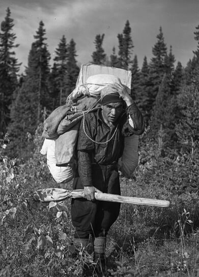 Picture of a hunter called Jos Color carrying a very heavy load on his back and his rifle in the right hand
