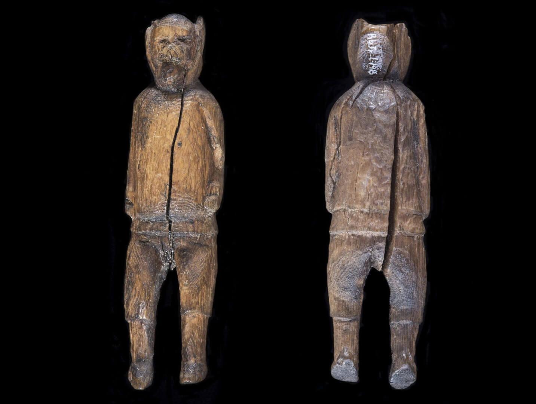 Photographie d'une sculpture dorsétienne représentant un homme. Le manteau à col élevé est dépourvu de capuchon.
