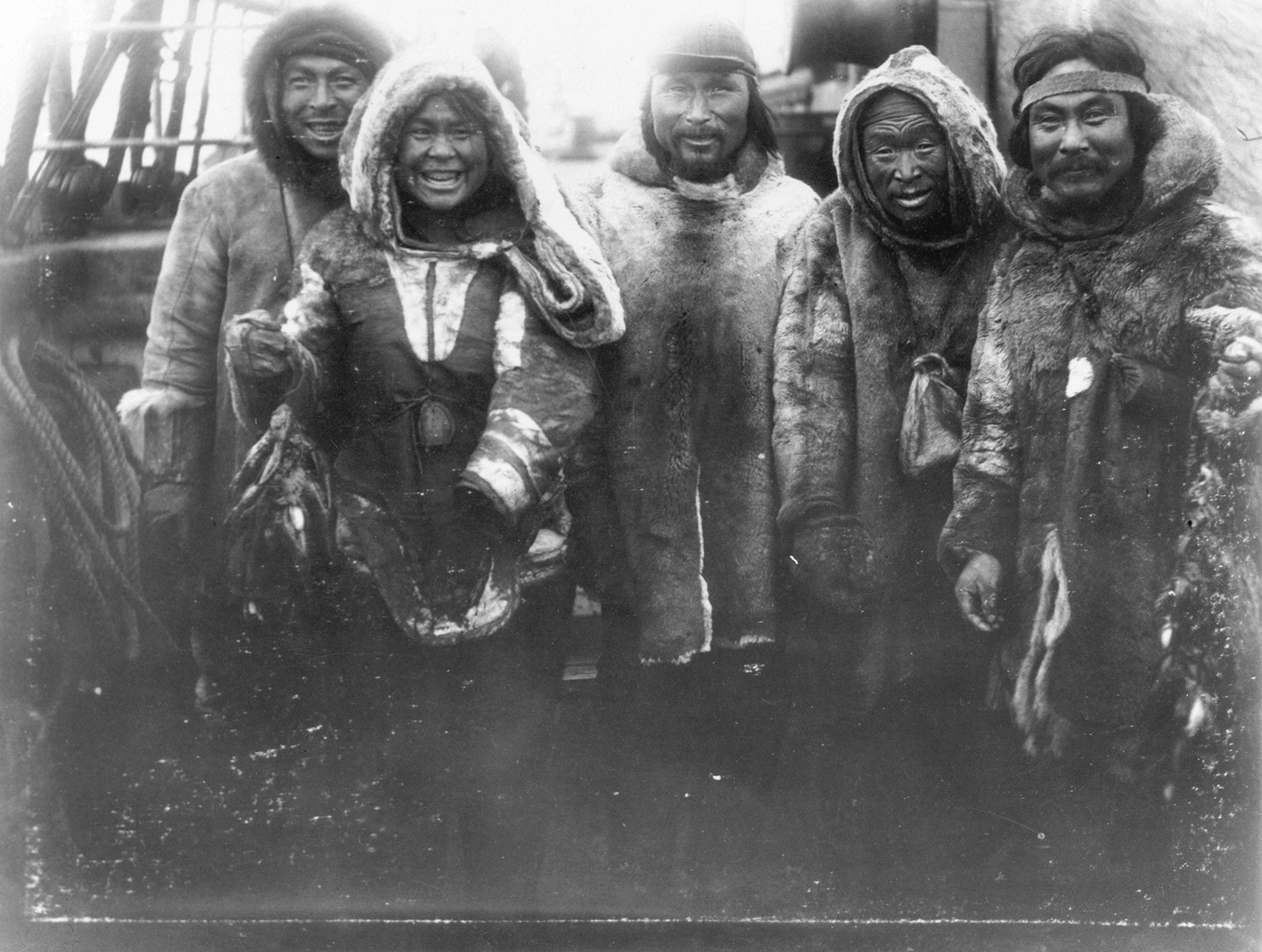 Photograph of Inuit taken at Douglas Harbor during the Wakeham expedition. Kangiqsujuaq, 1897. All the individuals are smiling and proudly wearing skin clothing.