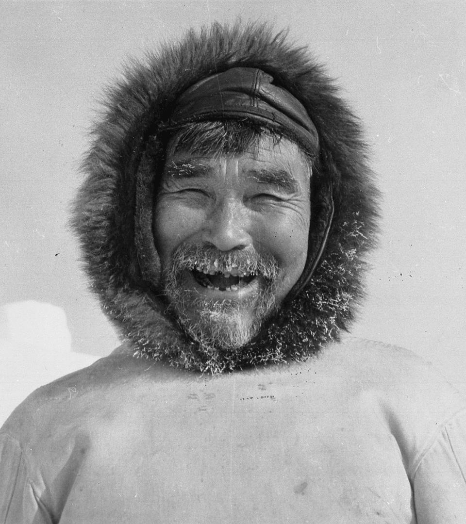 Photographie de Qamuraluk Qasilinaq. Kangiqsujuaq, 1960s. Homme souriant, il porte un vêtement dont le capuchon présente une bordure de fourrure.