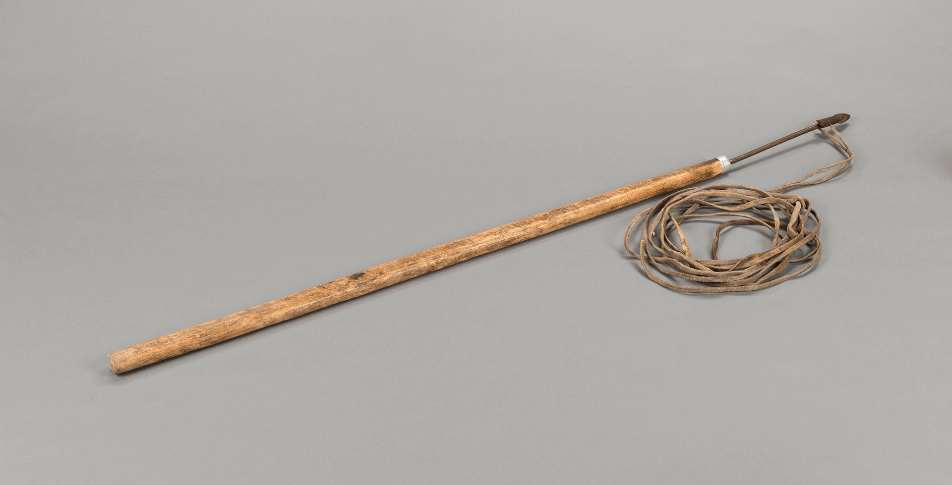Photographie d'un harpon avec lanière en peau de phoque barbu. Une flèche détachable est fixée à une des extrémités.