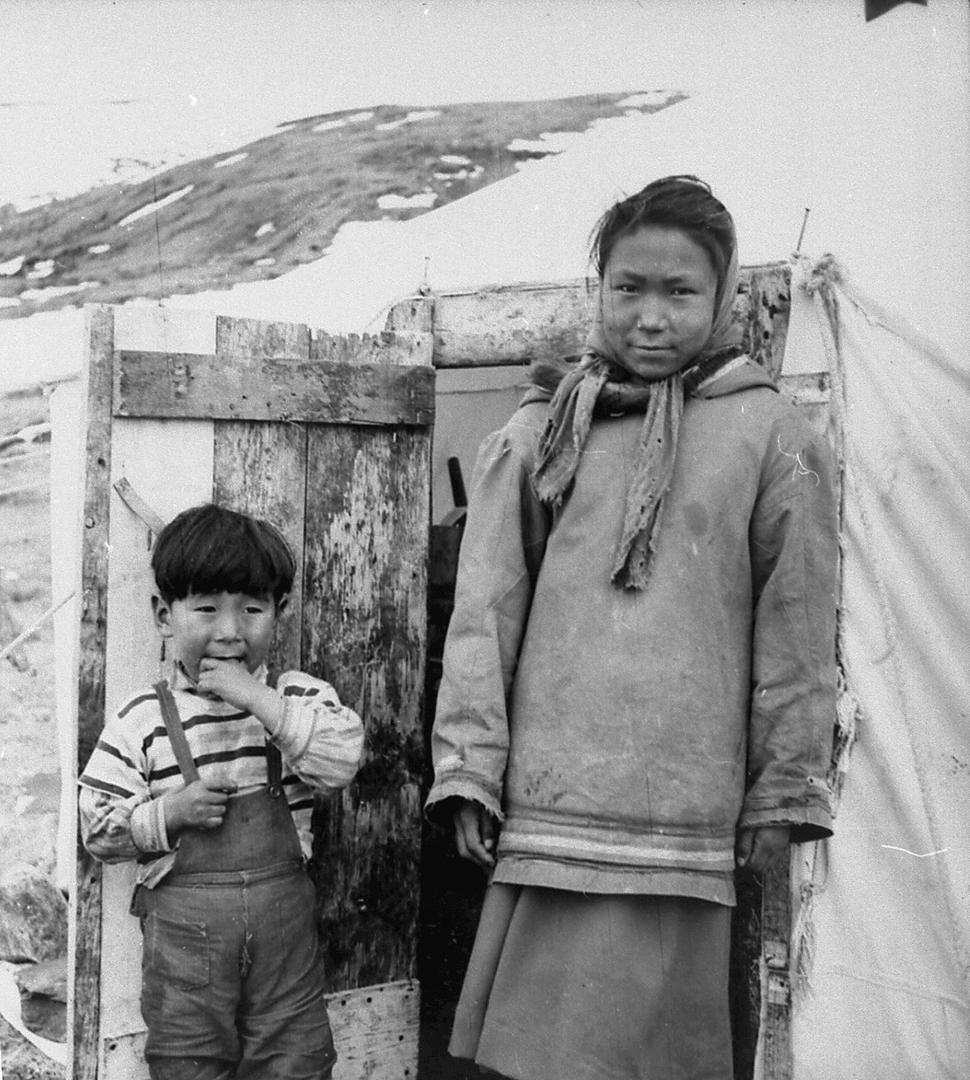 Photographie d'un jeune garçon nommé Pita Jaaka et d'une jeune femme nommée Maggie Qisiiq. Ils posent fièrement devant la porte d'une tente de toile.