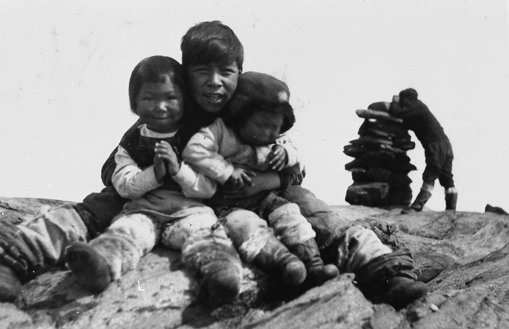 Photographie d'enfants assis côte à côte sur un rocher. Derrière, un homme debout est appuyé sur un inukshuk.