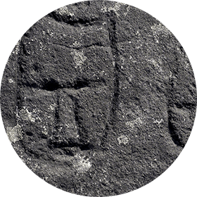 Photograph of a carved horned head and a round-shaped head