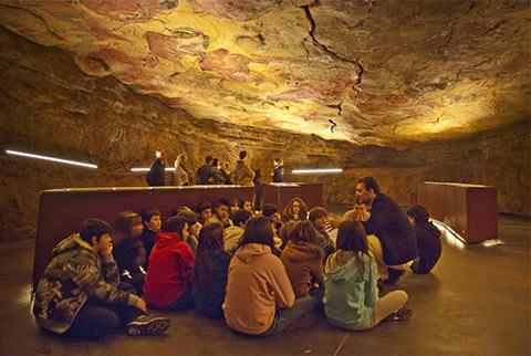 Un groupe de jeunes visiteurs est assis dans une grotte et écoute un professeur, dans une grotte où l'on voit plusieurs bœufs peints au plafond.