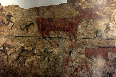 Red oxen and black human figures that seem to run, painted on an ancient wall.