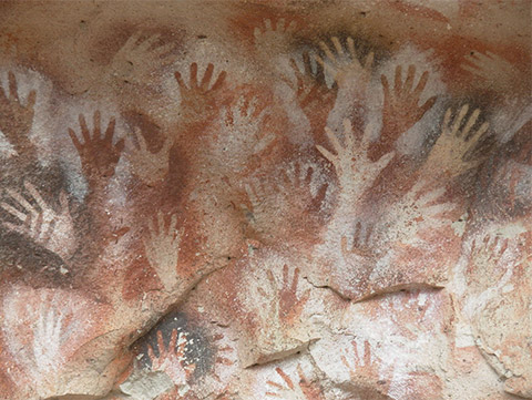 Several superimposed handprints, painted on the rock surface in negative with ochre or white pigments.