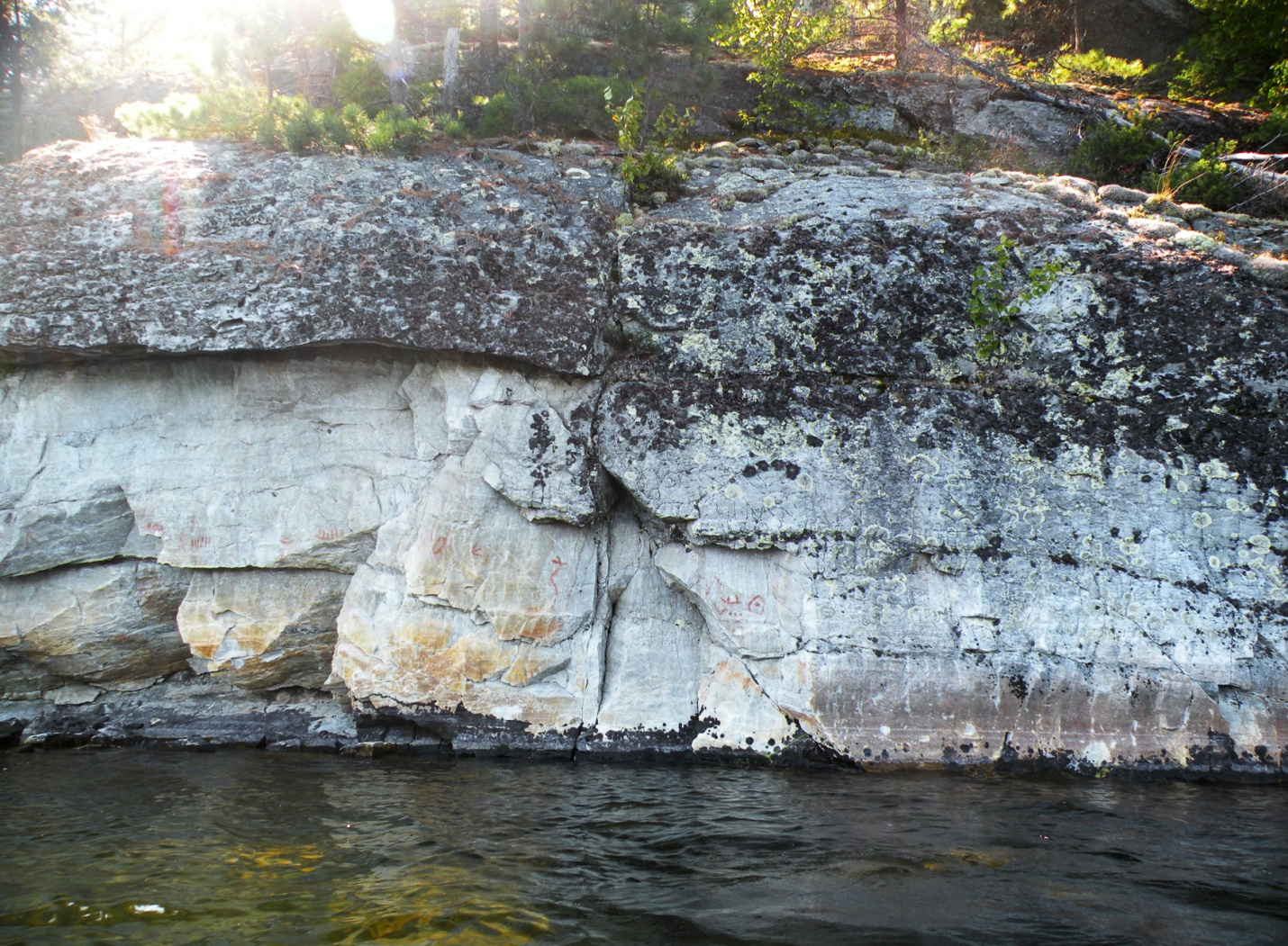 Picture of the Diamond Lake site, in Ontario, Canada. A horned snake, canoes and a bird track are painted on a rock outcrop.