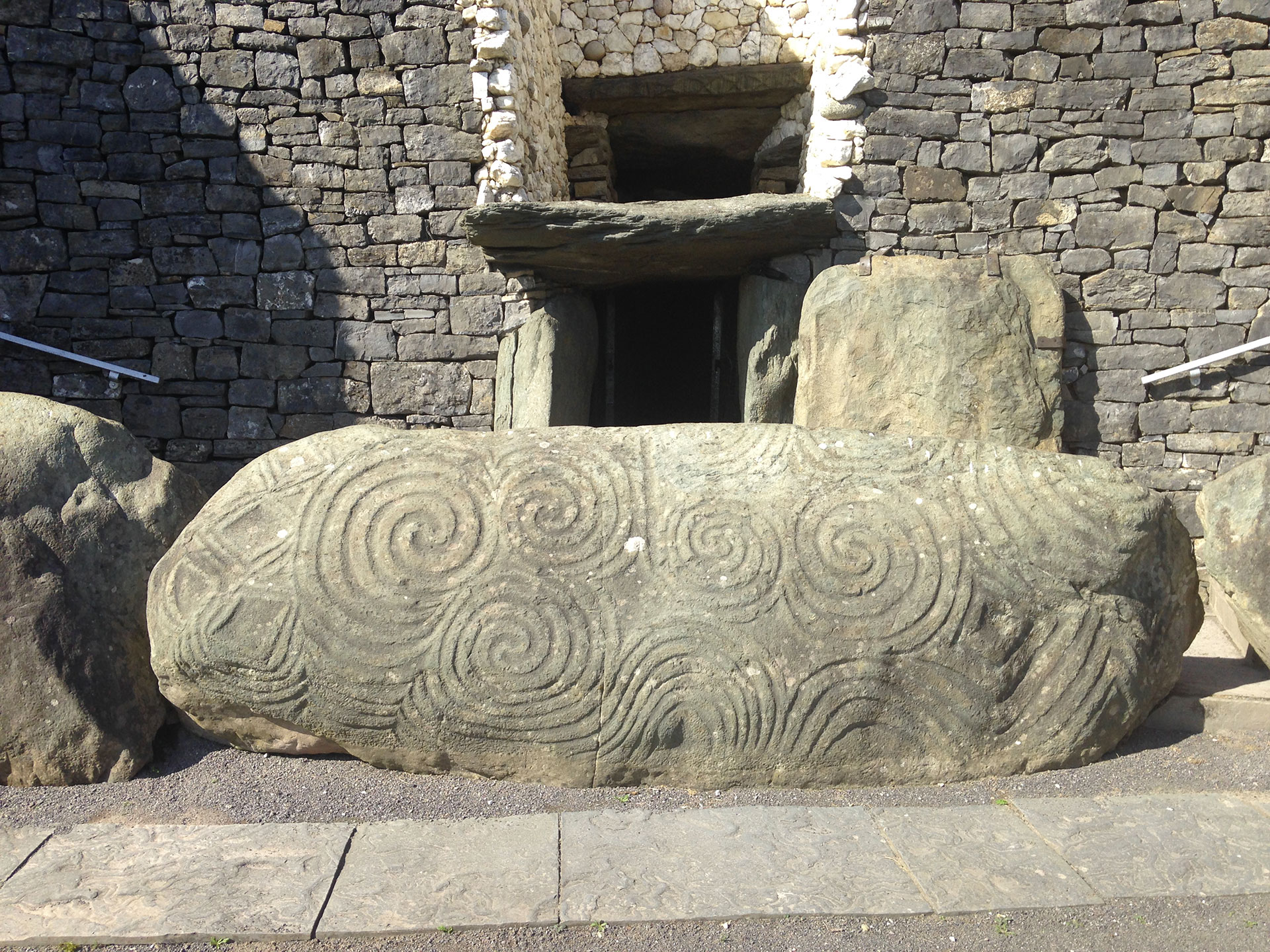 Picture of a boulder featuring spiral carvings and other geometric shapes at the Newgrange site, Brú na Bóinne complex, Ireland