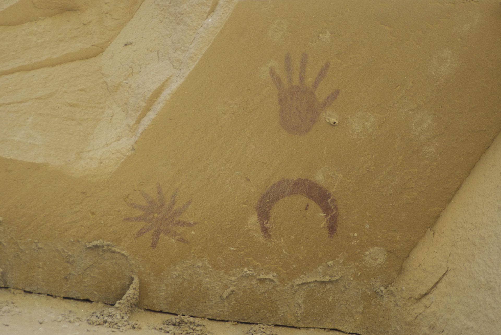 Photographie de pictogrammes représentant la lune, une grande étoile et l'empreinte d'une main. Site de Chaco Canyon, Nouveau-Mexique, États-Unis d'Amérique.
