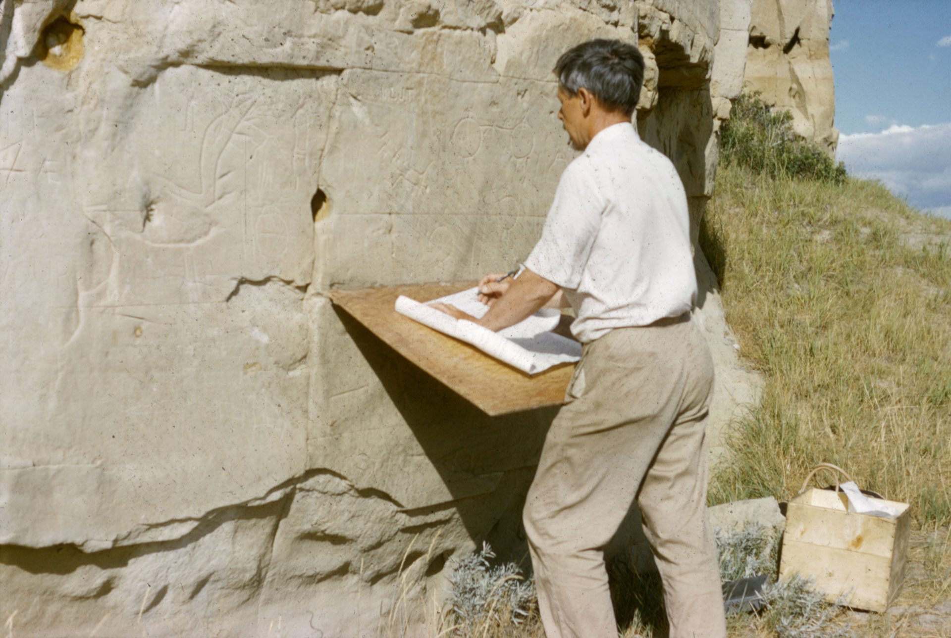 Picture of Selwyn Dewdney checking tracings of petroglyphs at Áísínai'pi, in August 1960