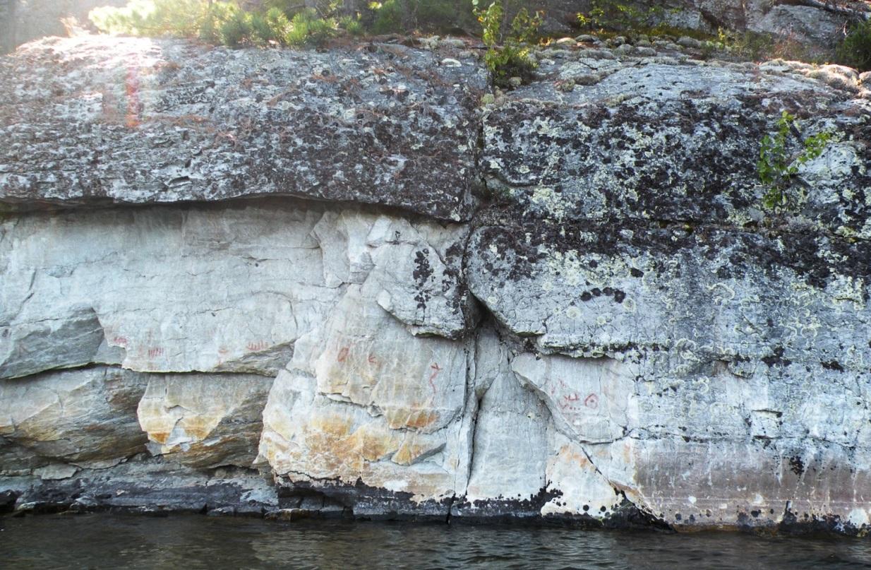 Photographie du site de Diamond Lake en Ontario, au Canada. Sur un afleurement rocheux sont représentés un Serpent cornu, des canoës et une empreinte de patte d'oiseau.