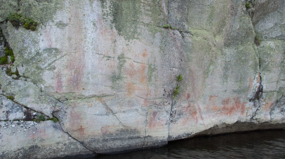 Painted panel at the Bloodvein River site in Ontario. This site has many images, including an anthropomorph holding a smaller being, canoes and handprints.